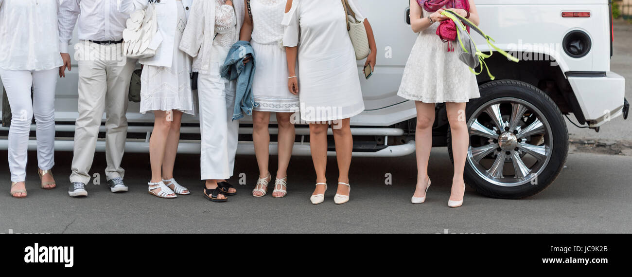 People dressed in white posing next to limousine. Body parts, white party - Stock Image