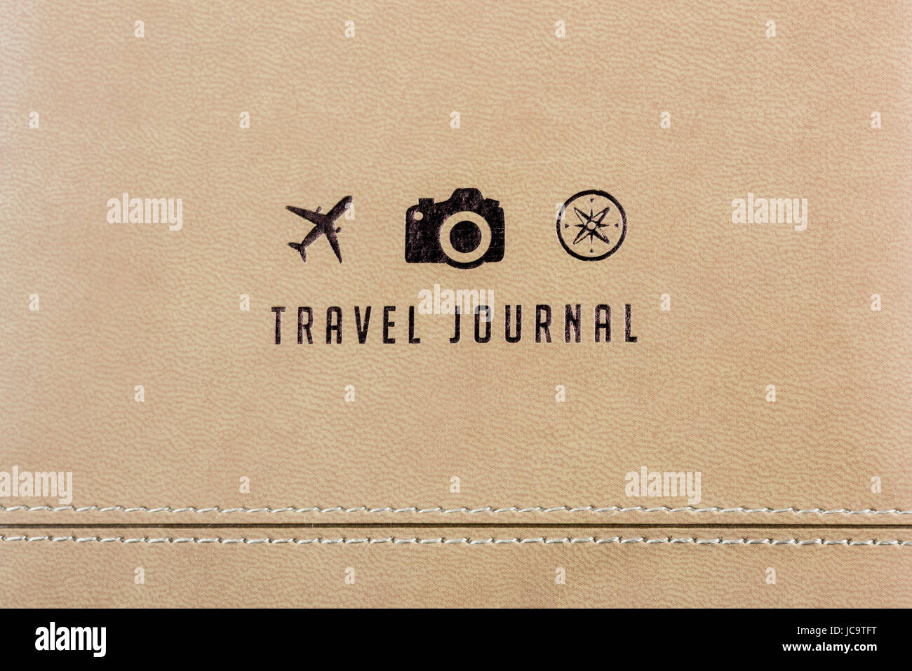 close up of a travel journal cover with 3 small logos a plane a