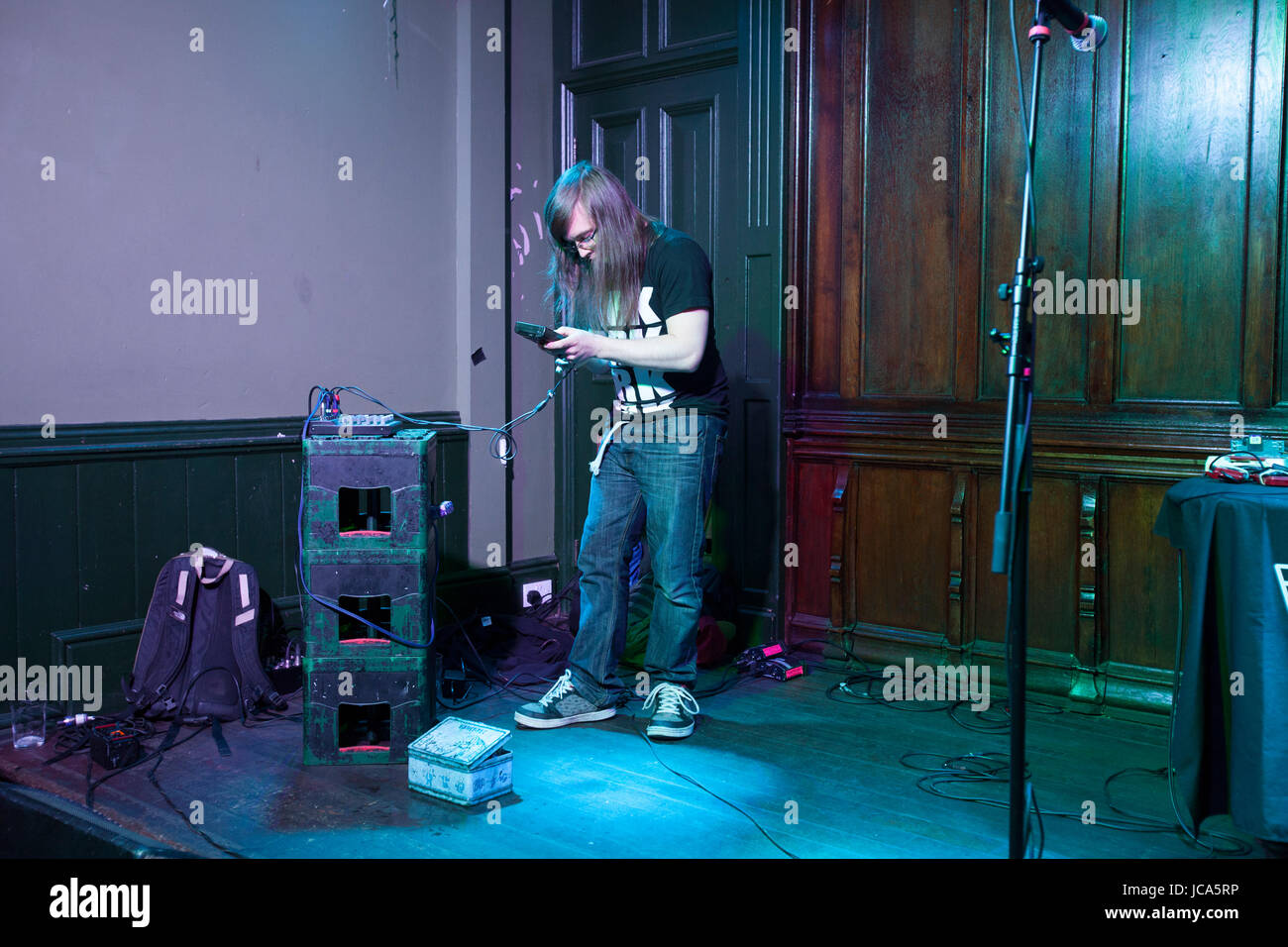 D'jays playing live. Making music with Gameboys. Chiptune d'jays. Long haired, guy, male, dj - Stock Image