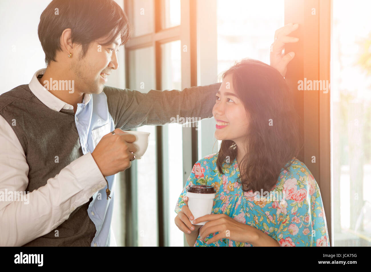 couples of younger asian man and woman with coffee cup in hand toothy smiling face happiness and relaxing discussing - Stock Image
