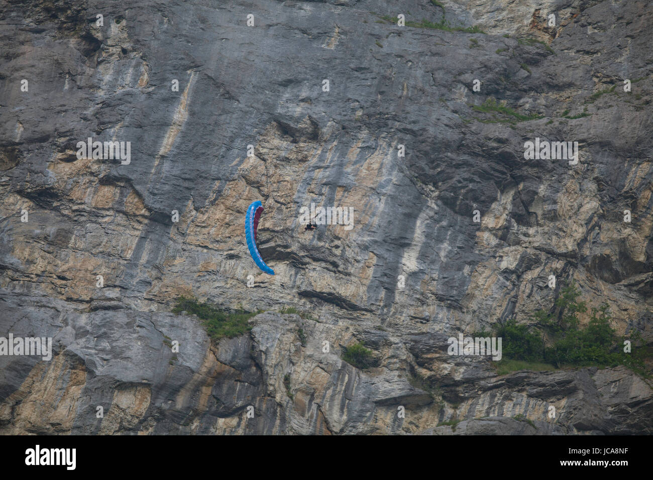 An unidentified person doing stunts with a parawing in front of a huge rock face.  Lauterbrunnen, Switzerland. - Stock Image