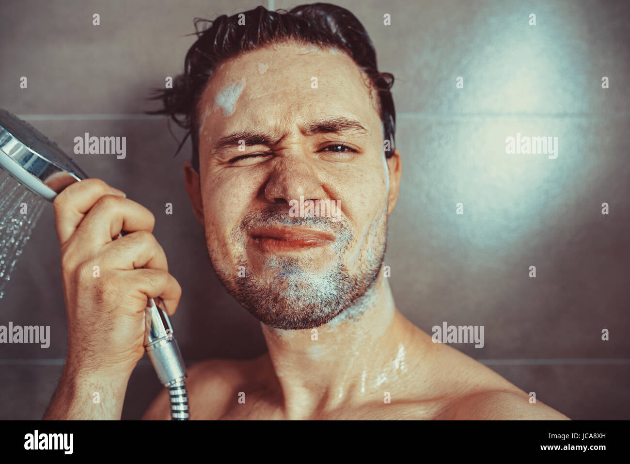 Young man washing head with shampoo in bathroom portrait. Unhappy emotions. - Stock Image