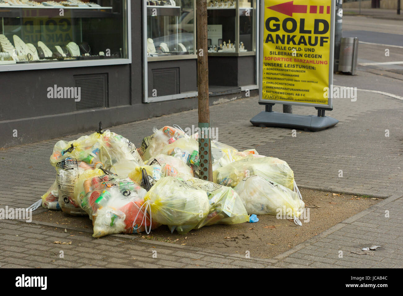 Yellow sacks for recyclable waste awaiting collection on pavement in front of shop, Mainz, Germany - Stock Image