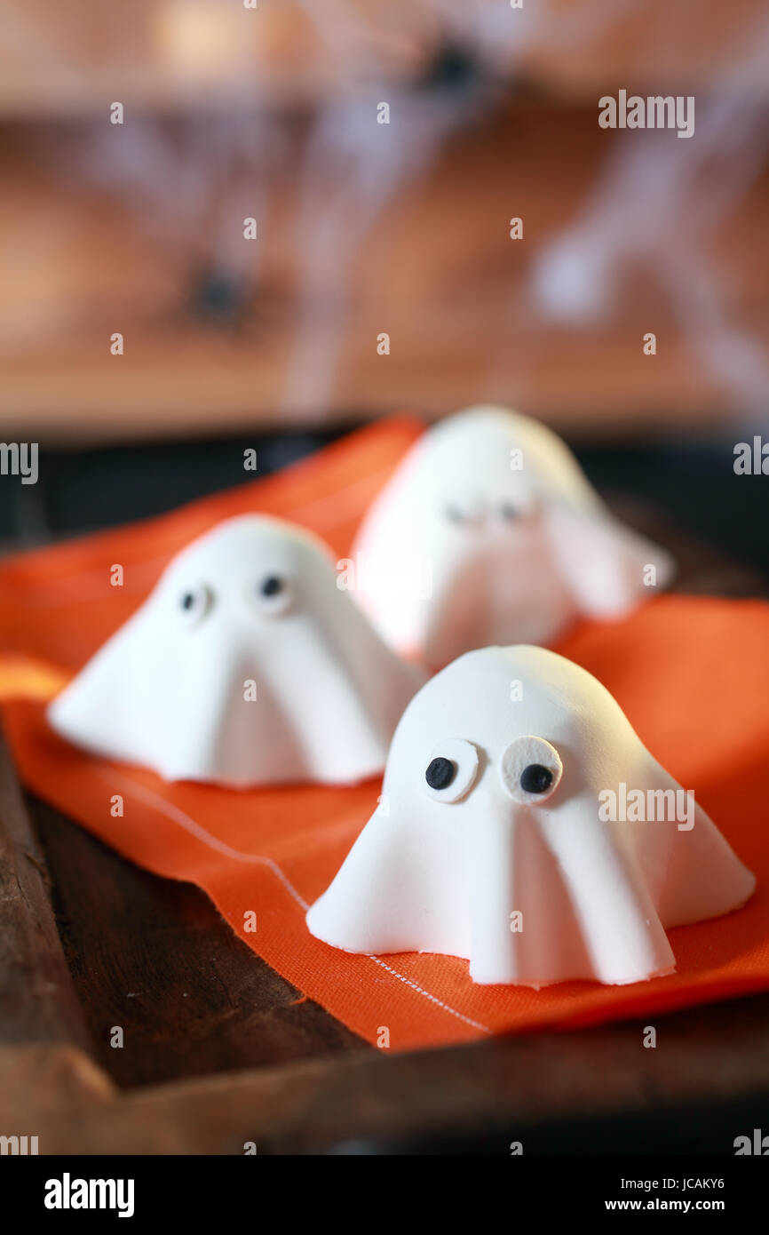 halloween party decorations from folded pastry dough in the shape of scary little ghosts with big eyes on an orange napkin with copyspace for your greeting