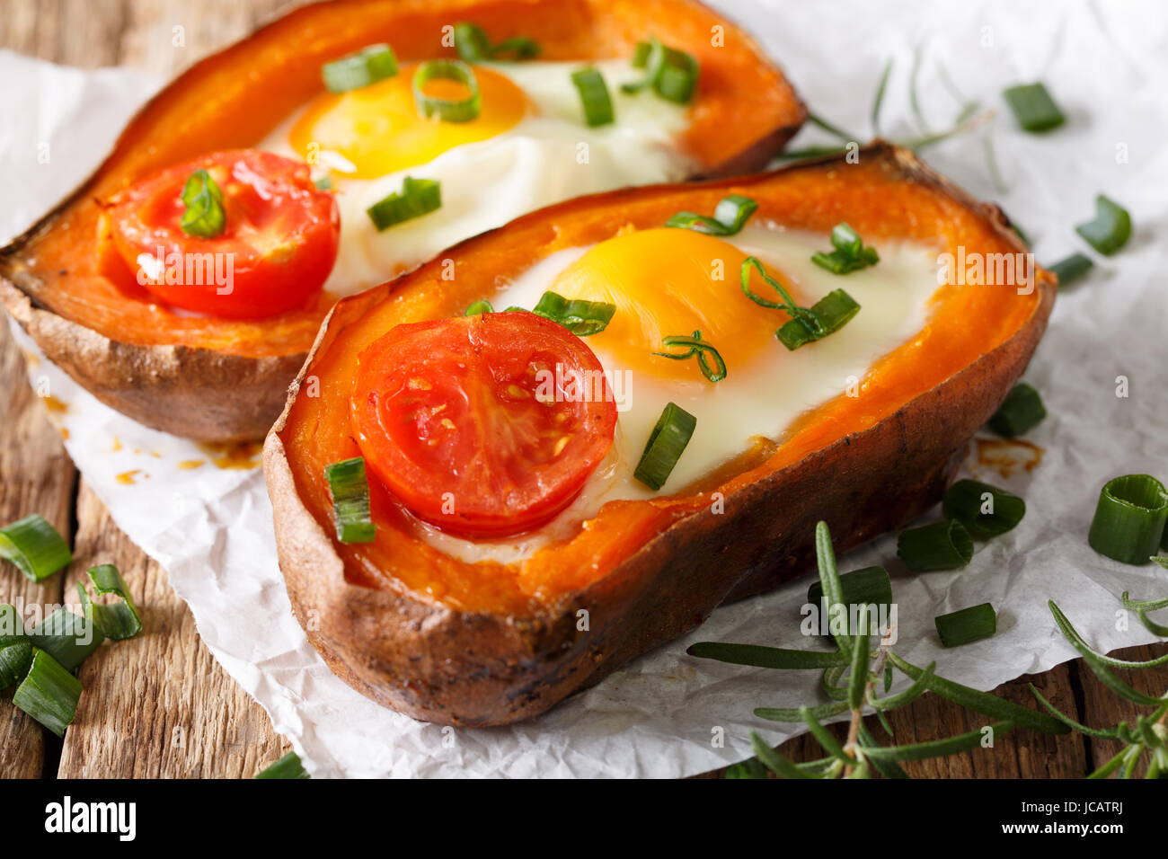 healthy baked sweet potato with fried egg and tomato close-up on the table. Horizontal - Stock Image