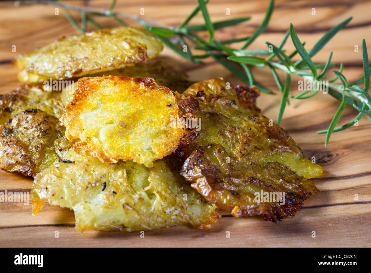 serving of potatoes that have been smashed and then baked with seasoned oil and spices as a side dish - Stock Image