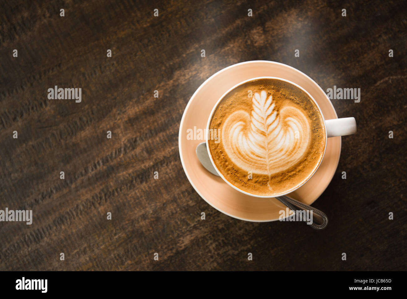 Close focus on cup of hot cappuccino coffee with latte art on dark brown wood table. - Stock Image