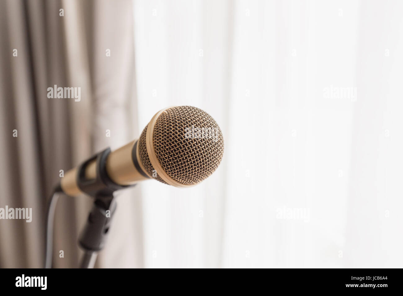 Close focus on classic gold wired microphone on stand with bright light from window. - Stock Image