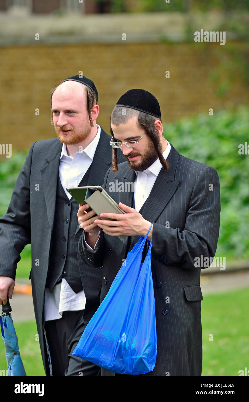 London, England, UK. Orthodox / Hasidic Jews with shopping and a tablet computer - Stock Image