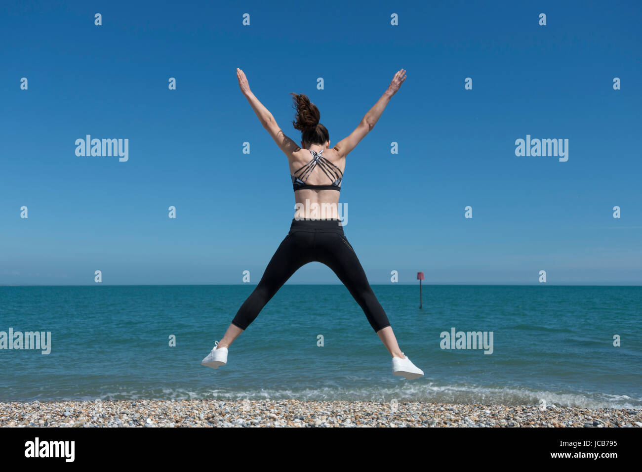 woman doing a star jump on the beach - Stock Image