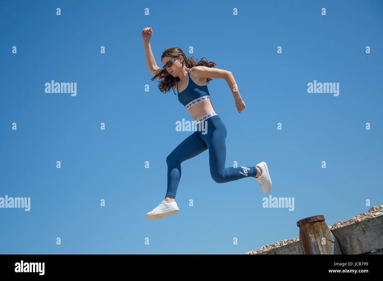 woman doing a running  jump on the beach - Stock Image