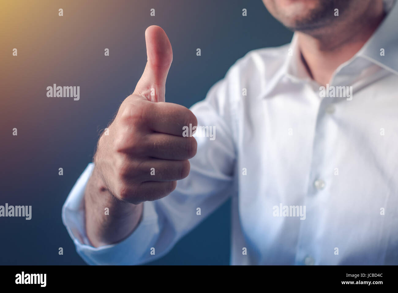 Businessman approving with raised thumb up gesture, business person in white shirt with roll up sleeves emphasizing - Stock Image