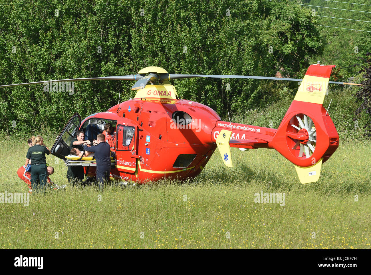 West Midlands Air Ambulance medical crew and NHS paramedics lifting a road accident patient into the helicopter - Stock Image