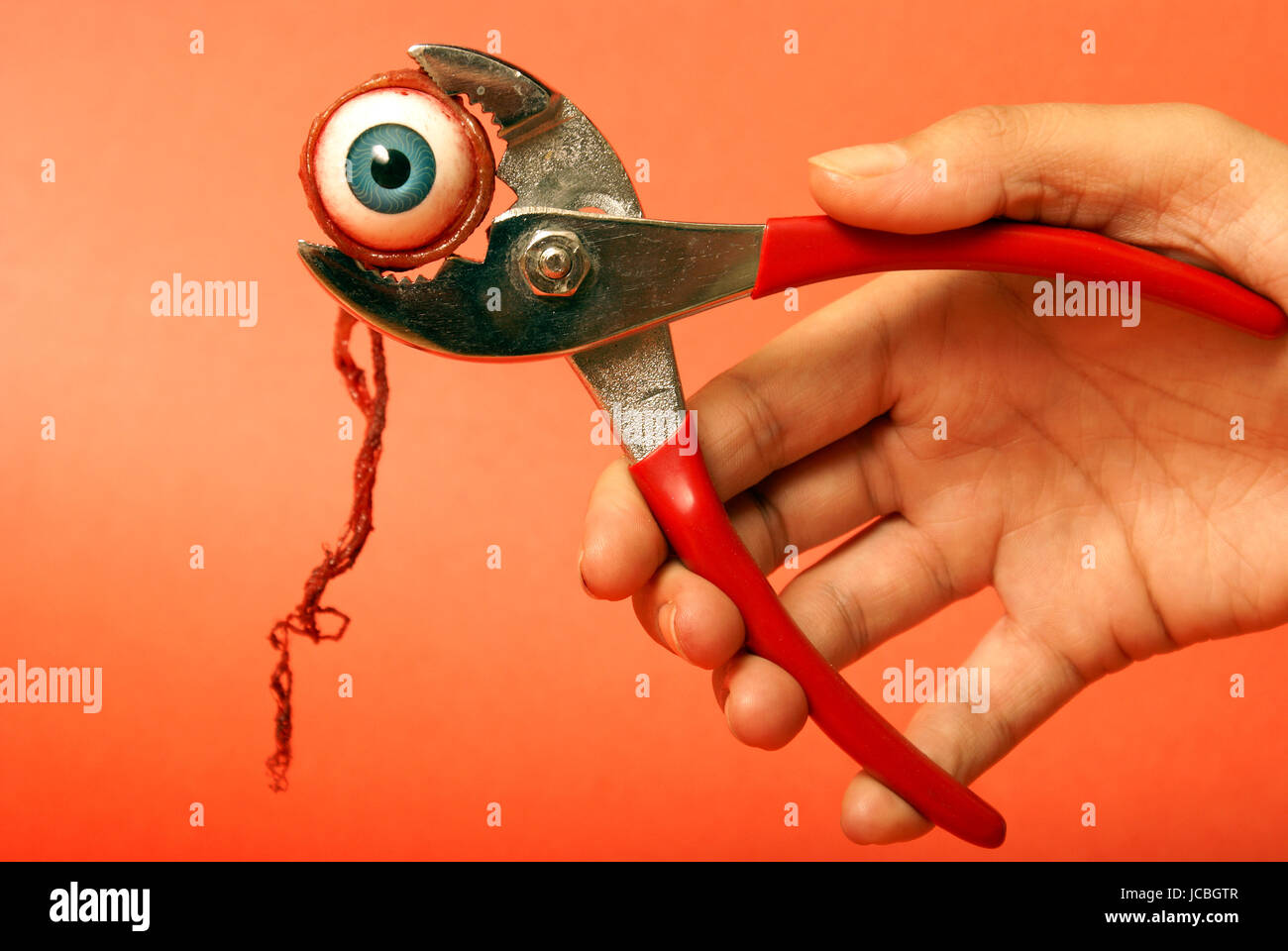 An eyeball feels the squeeze of a pair of pliers. - Stock Image