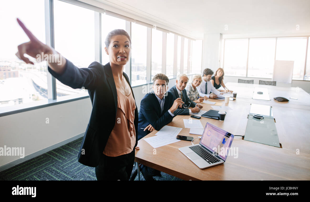 Business meeting and presentation in modern conference room. Asian businesswoman showing something important to - Stock Image
