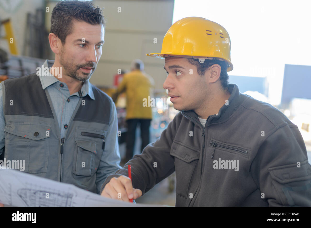 male worker showing something to co-worker at his notebook papers Stock Photo