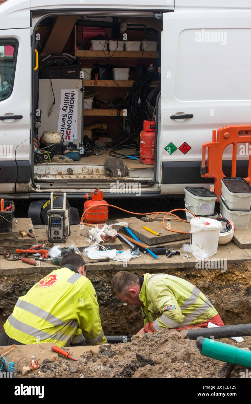 Technicians working in an excavation on electrical power cables being jointed after installation - Stock Image