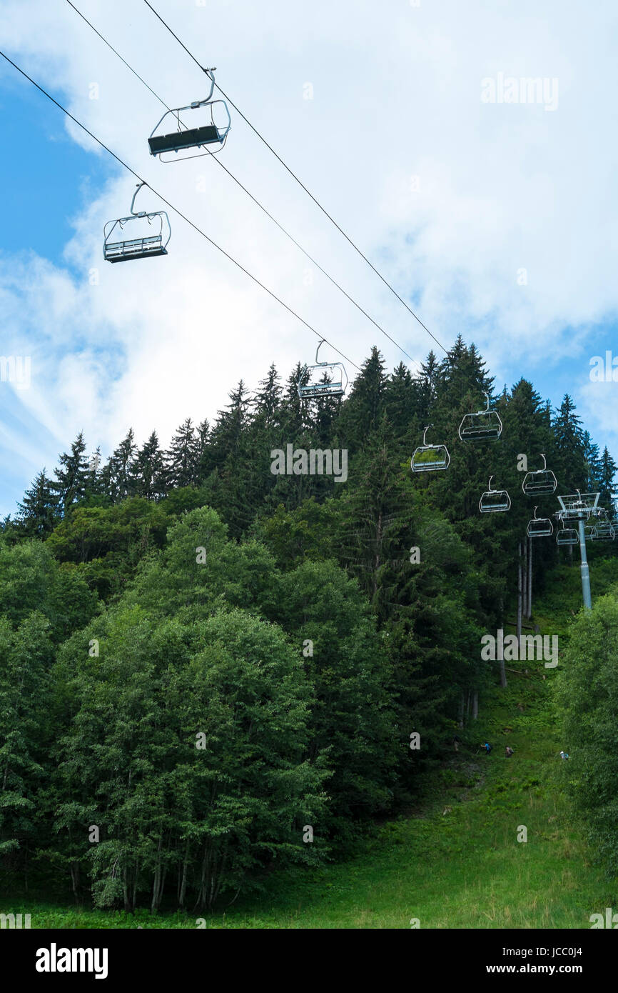 Low angle shot of alpine air lift with trees in the background - Stock Image
