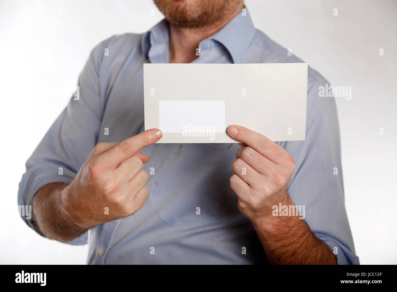 Man in a blue shirt holds a letter into the camera Stock Photo