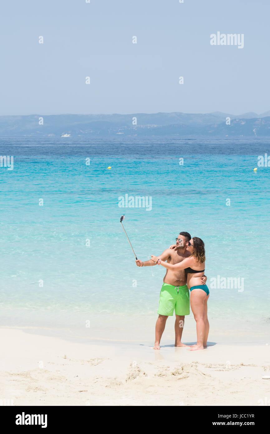 Couple taking selfies using selfie stick on beach - Vrika Beach Antipaxos, Greece - Stock Image