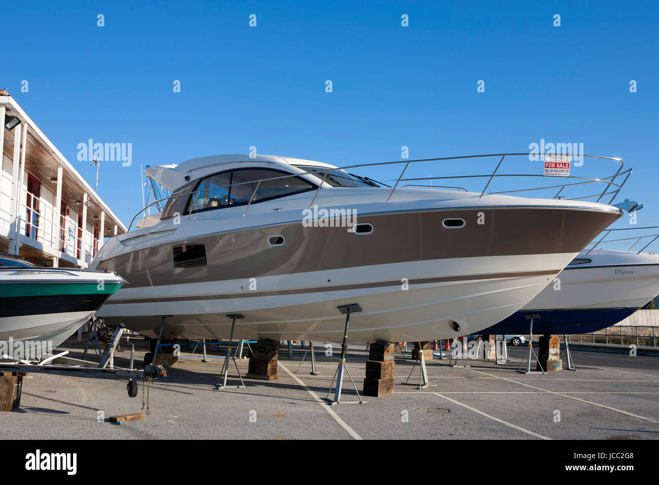 large luxury motor boat yacht in dry dock marina on stilts for sale, Plymouth, Devon, England, UK - Stock Image