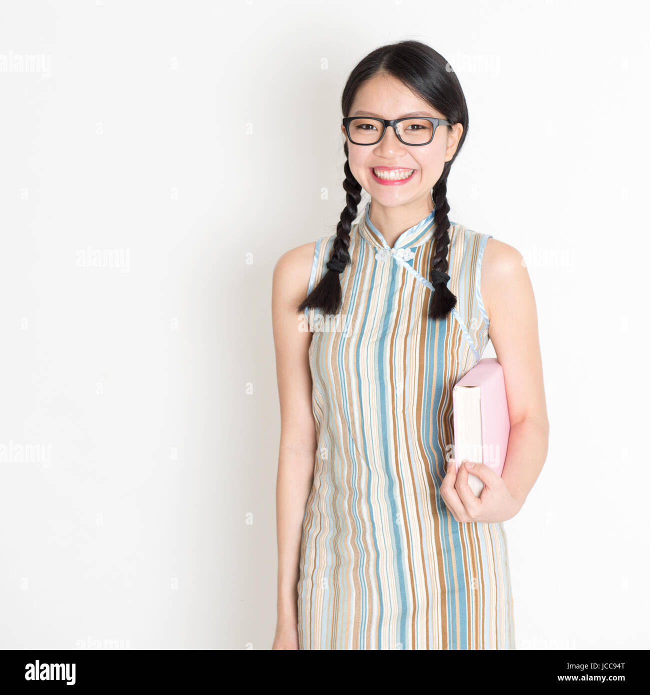 23dd890e9547 Portrait of Asian Chinese college girl hands holding text books in retro  revival style cheongsam standing on plain background.