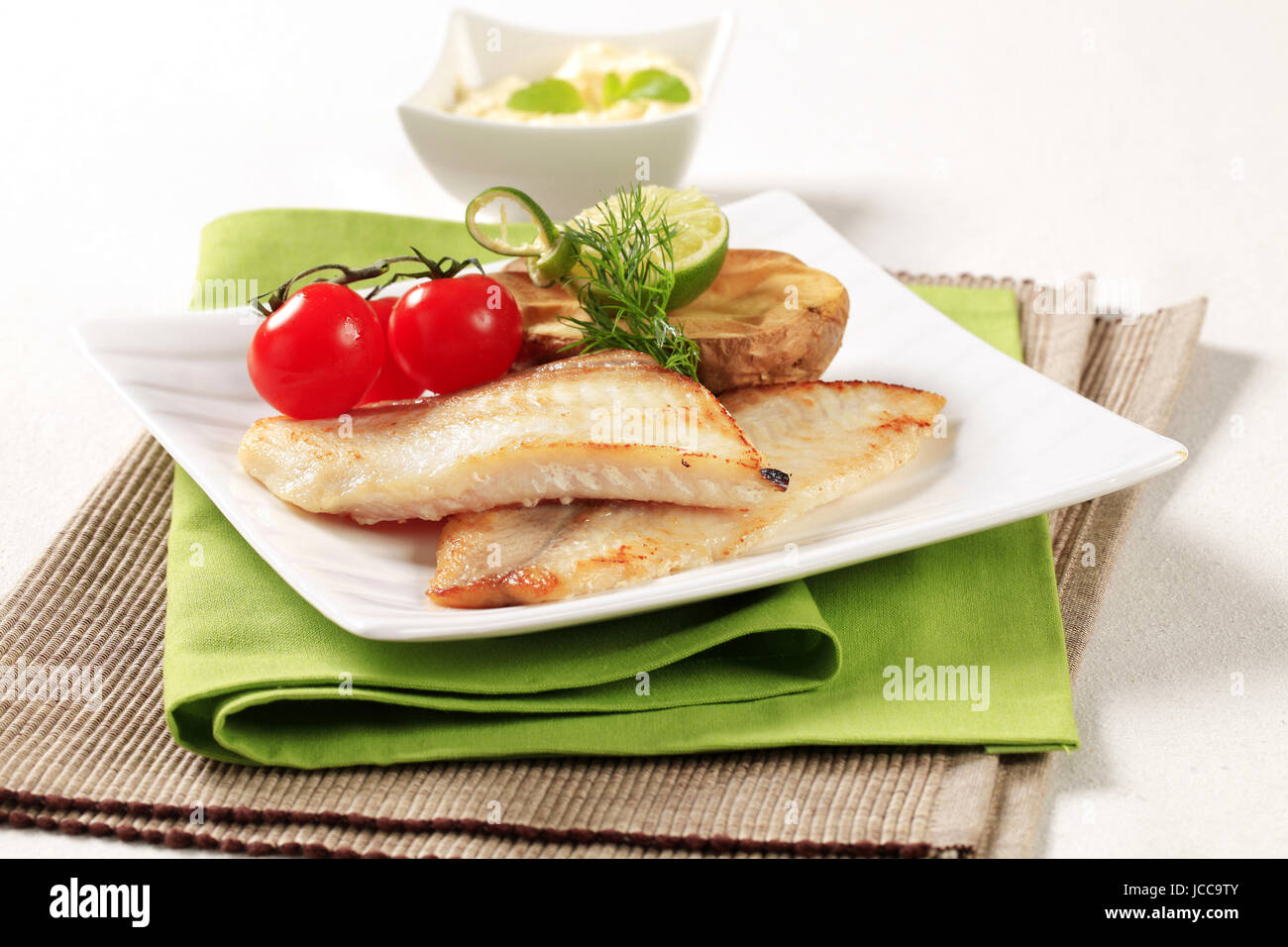 Pan fried fish fillets with roasted potato - Stock Image