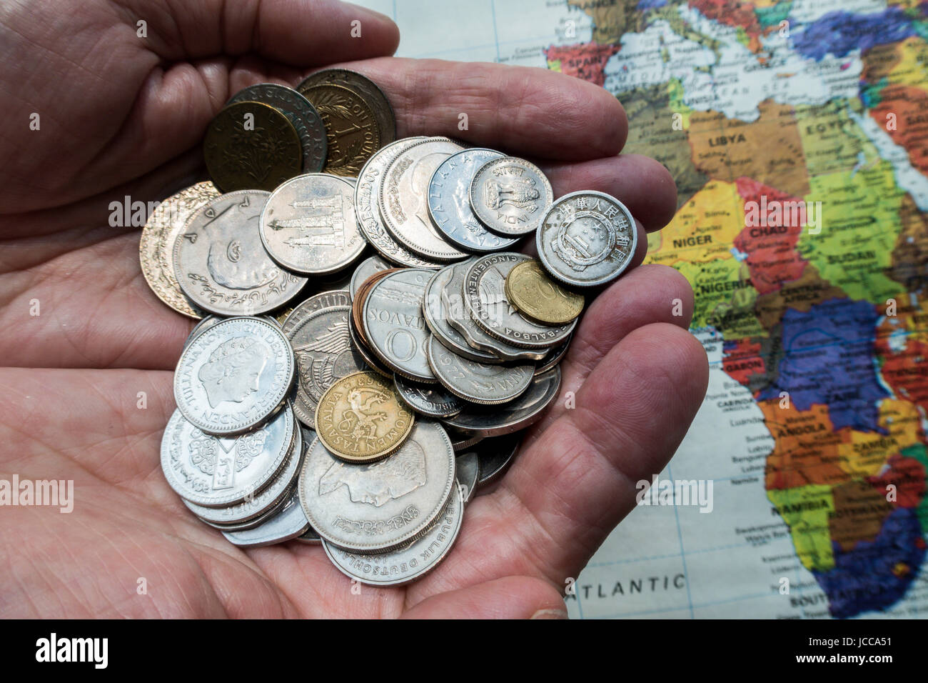 Hands Holding Multiple International Coins - Stock Image
