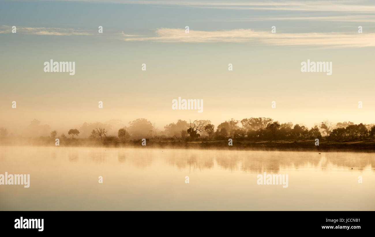 Early surface fog drifts acroos billabong, North Western Victoria, Australia. - Stock Image