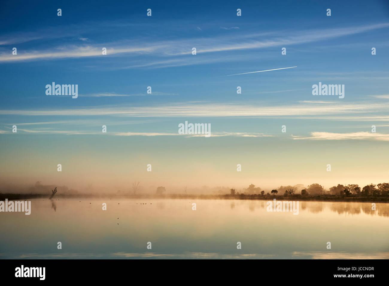 Early morning surface foog drifts over Billabong, Sunraysia Region, Victoria, Australia. - Stock Image