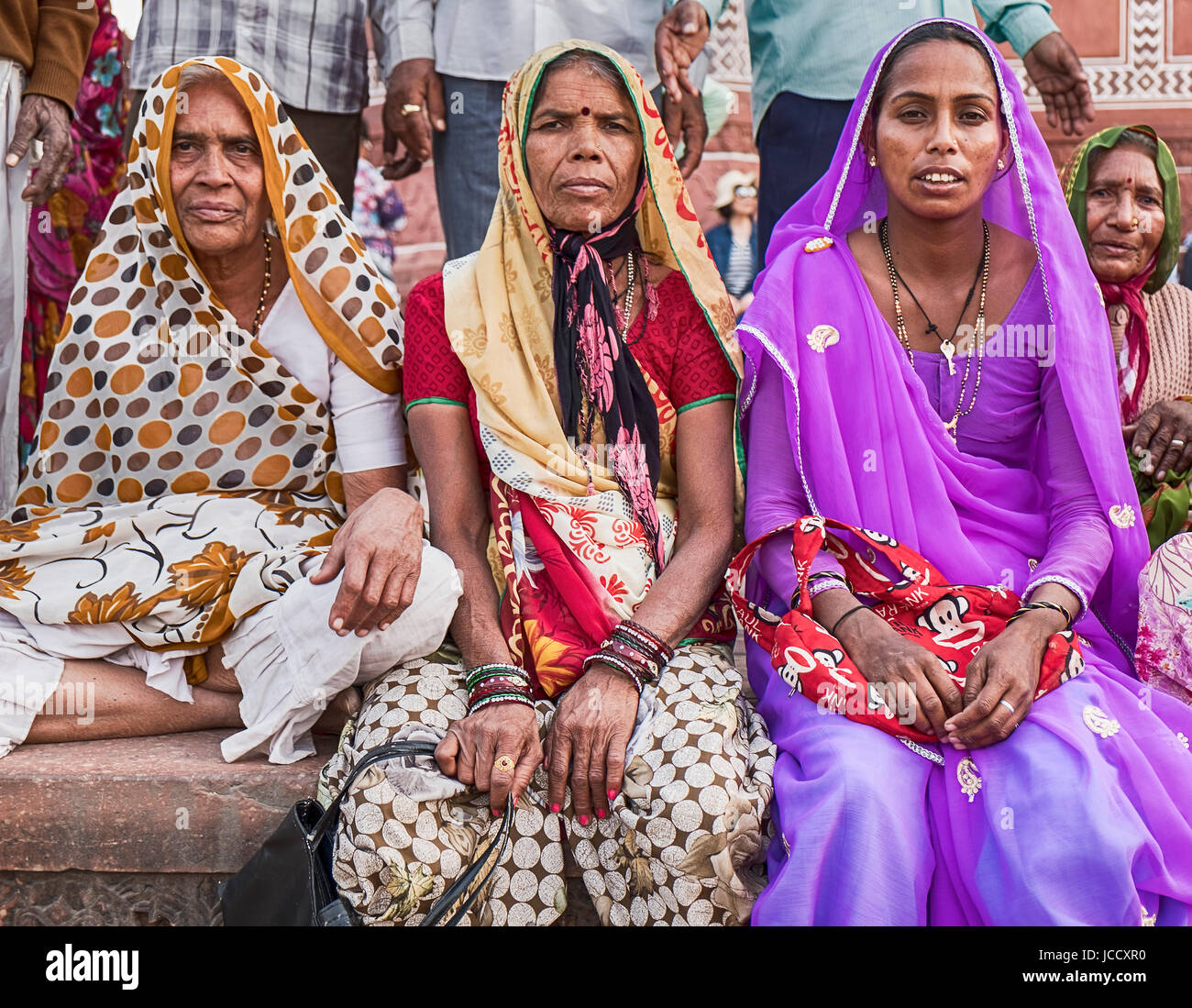 AGRA, INDIA - NOVEMBER 19, 2016: Three women in colorful saris and hijabs sit near the entrance to the Great Gate - Stock Image