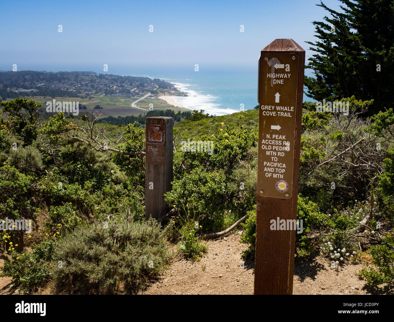 Signpost at junction of grey whale cove trail and old pedro mountain trail with view of montara beach and Montara, - Stock Image