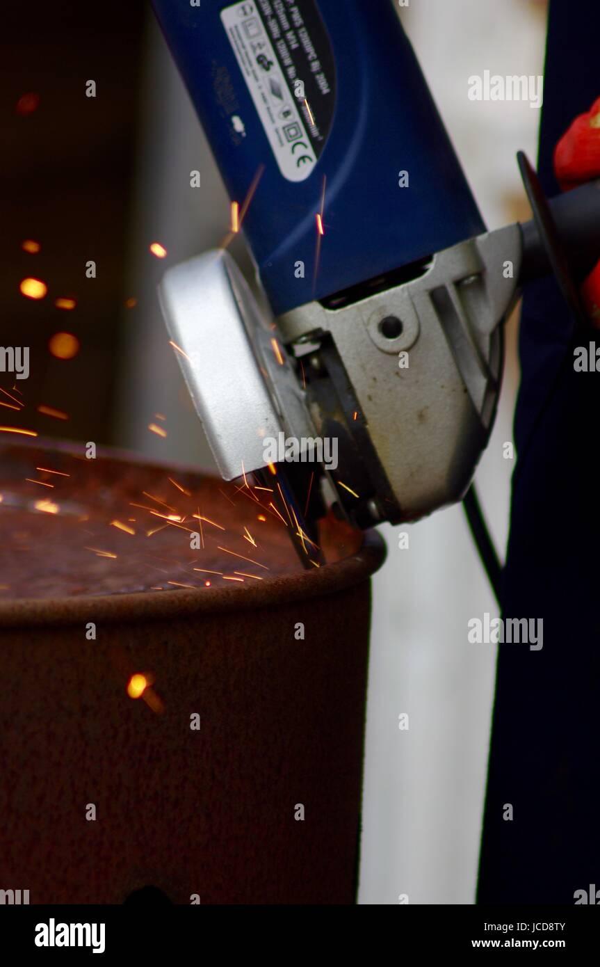 Angle Grinder, Cutting Oil Drum Lid, Orange Sparks.  Exeter, Devon. June 2016. - Stock Image