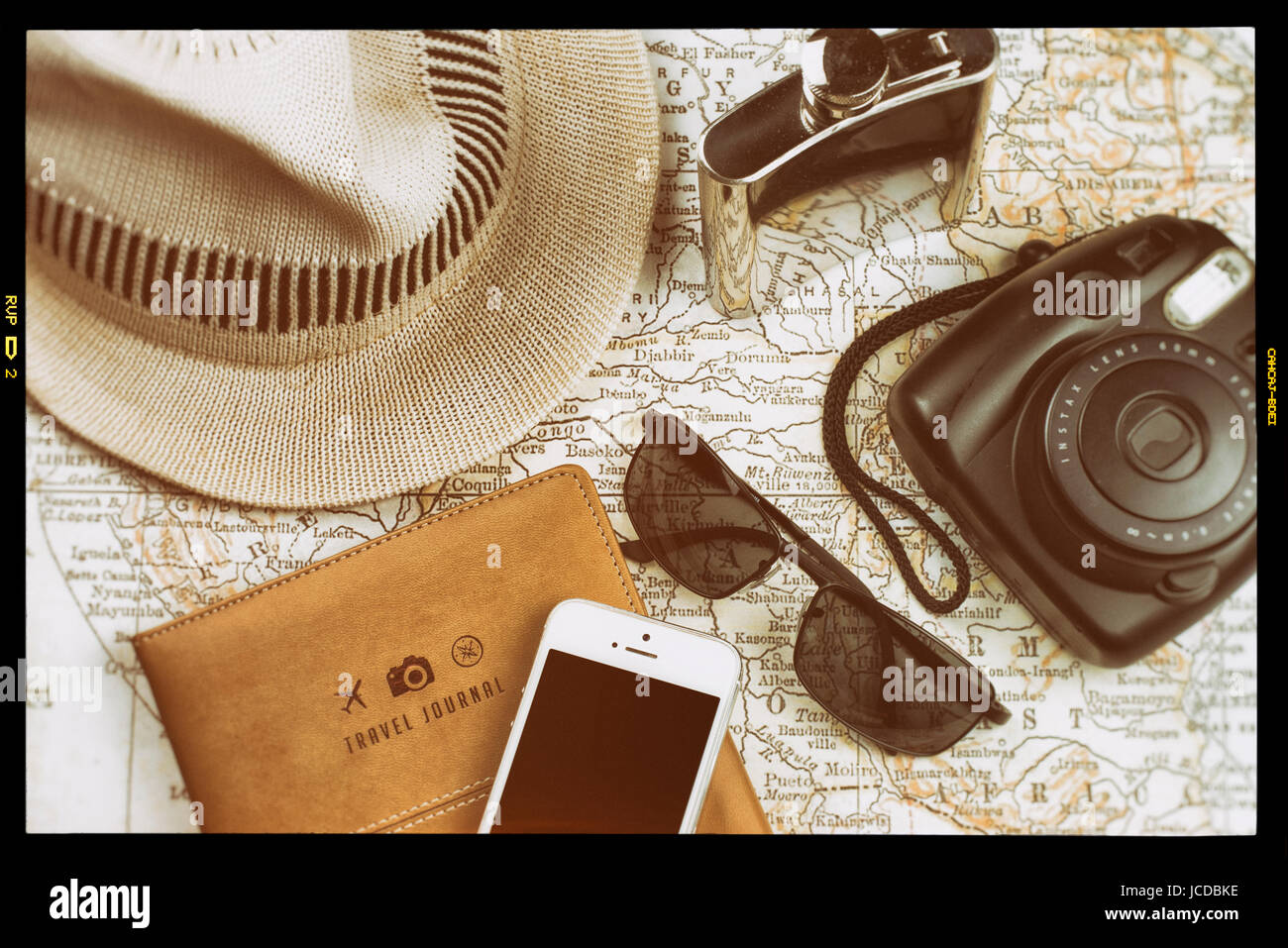 travel journal map with instant camera like polaroid mobile phone with black screen sunglasses flask in stainless steel and white hat