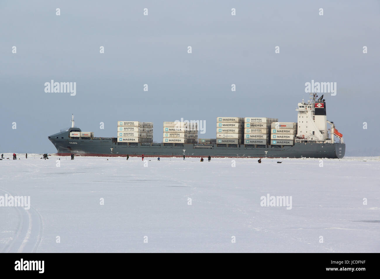 Commercial ship 'Calisto' is loaded with containers 'MAERSK sealand' through the ice at the destination - Stock Image