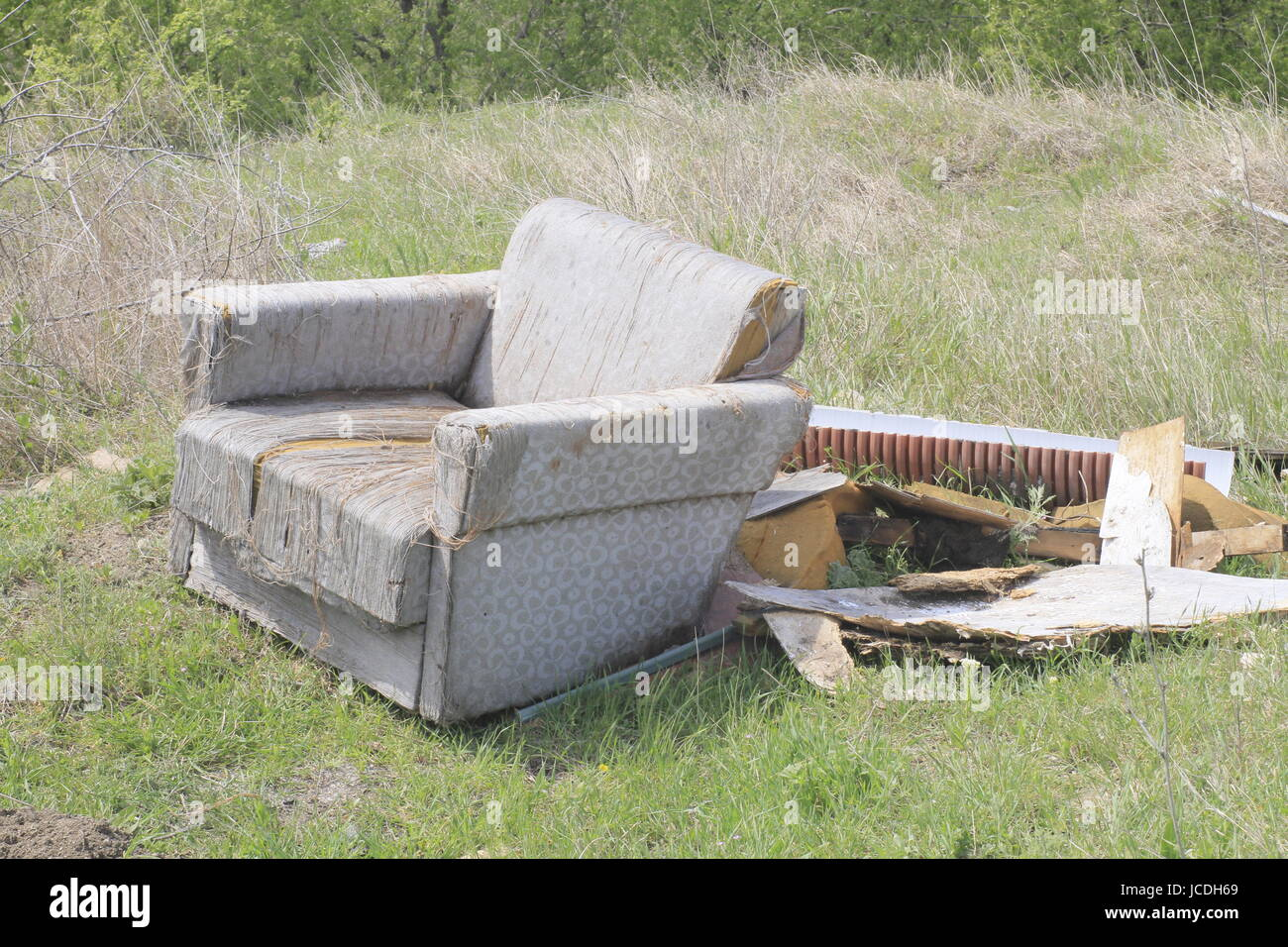 A picture or image showing an old seat or chair dumped rubbish in a field with other rubbish. - Stock Image