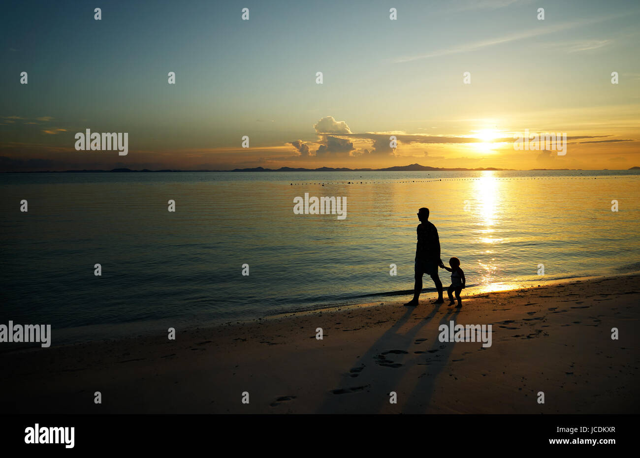 Father and his child walking on sunset beach , silhouette shot . - Stock Image