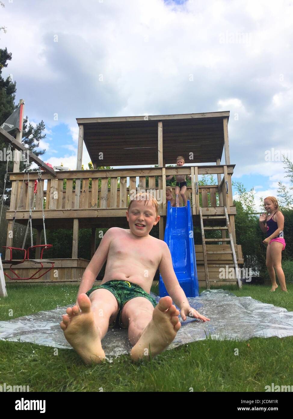 Children playing on a waterslide in the garden during summertime - Stock Image
