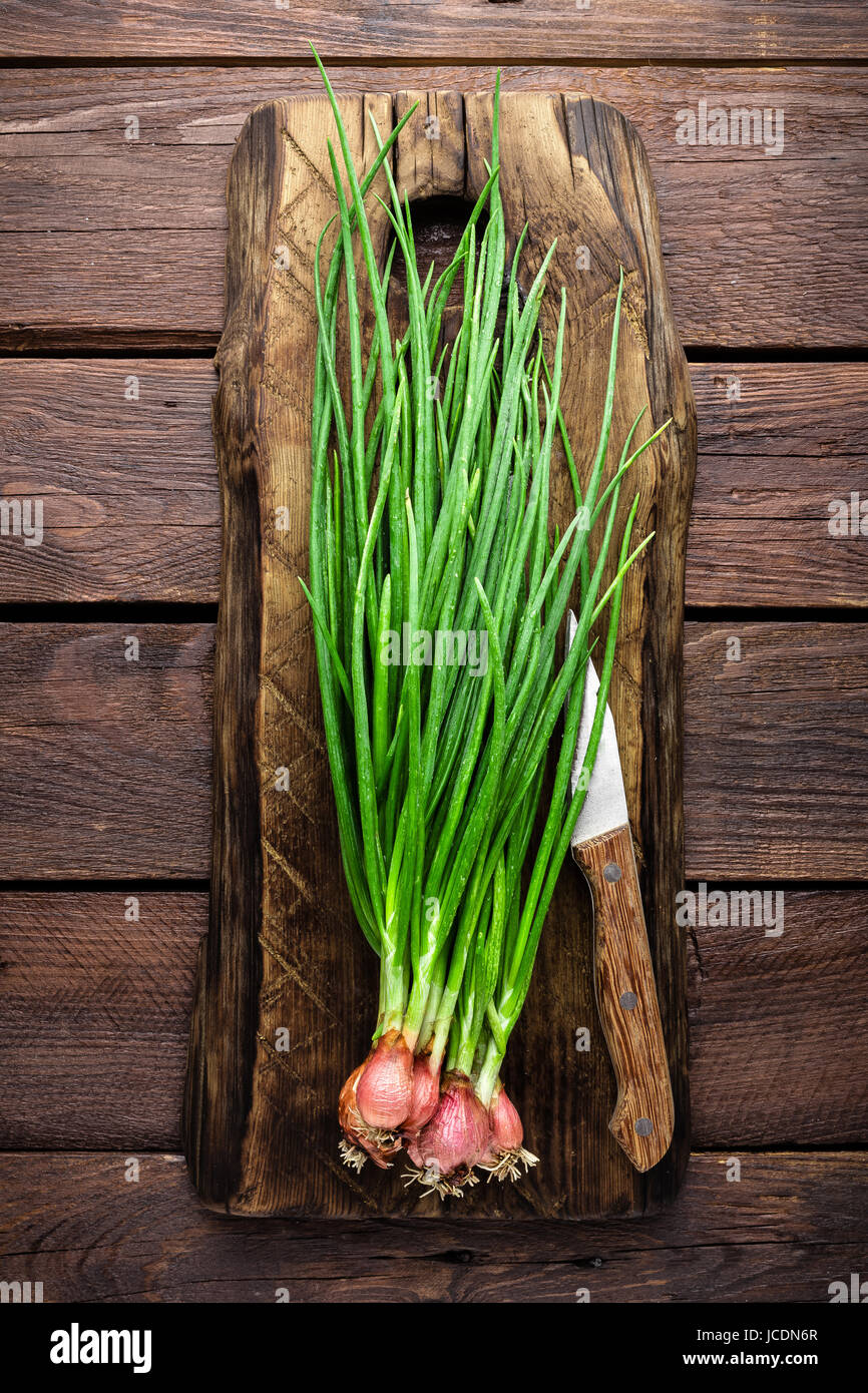 Green onion or scallion on wooden board, fresh spring chives - Stock Image