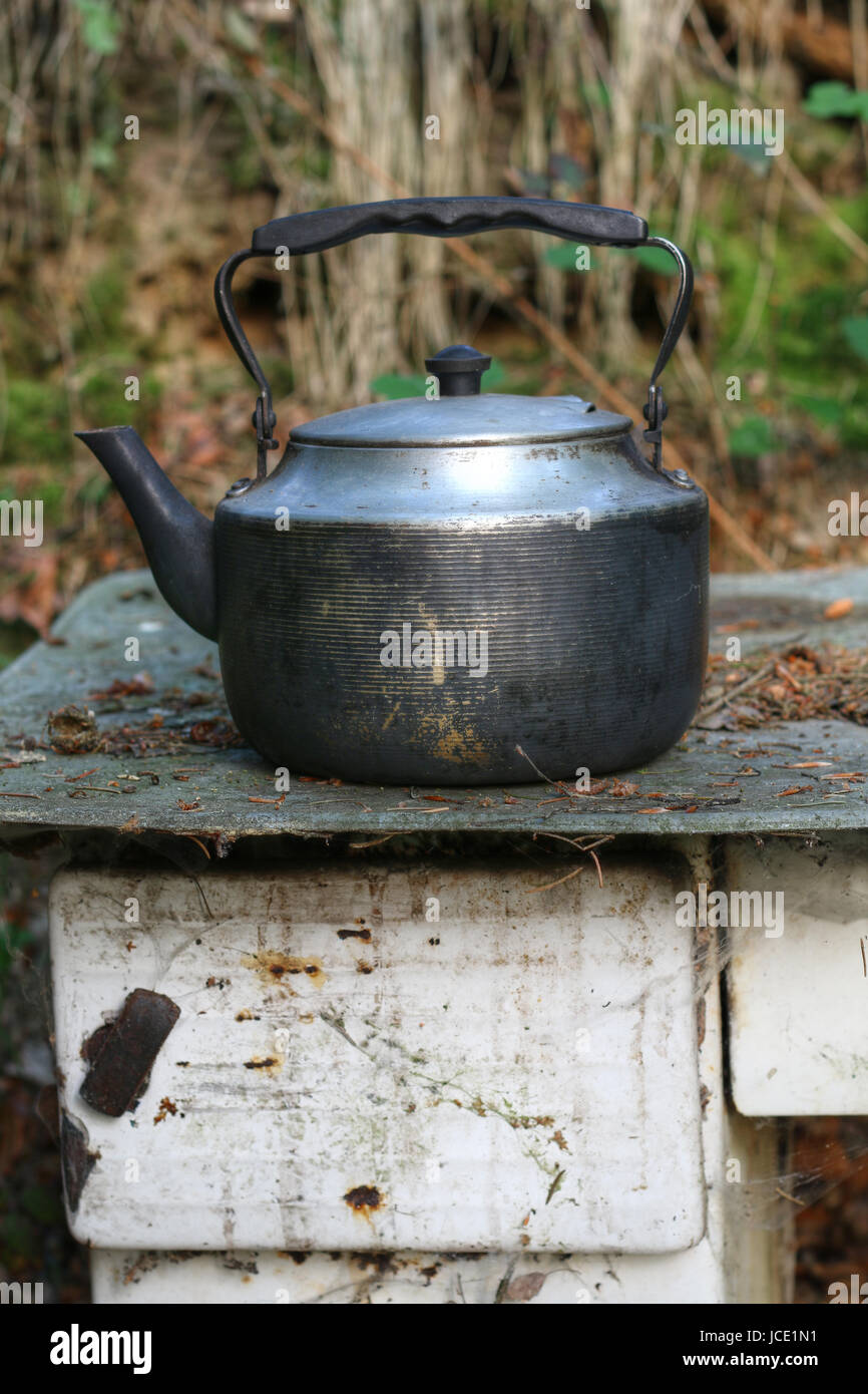 Detail of the old and worn teapot on old stove - Stock Image