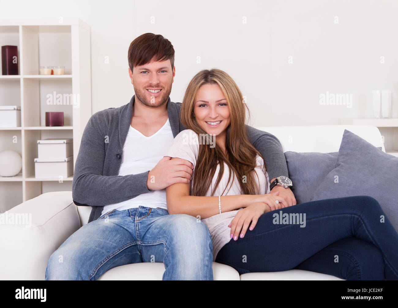 Couple sit on new couch bought at furniture shop. - Stock Image