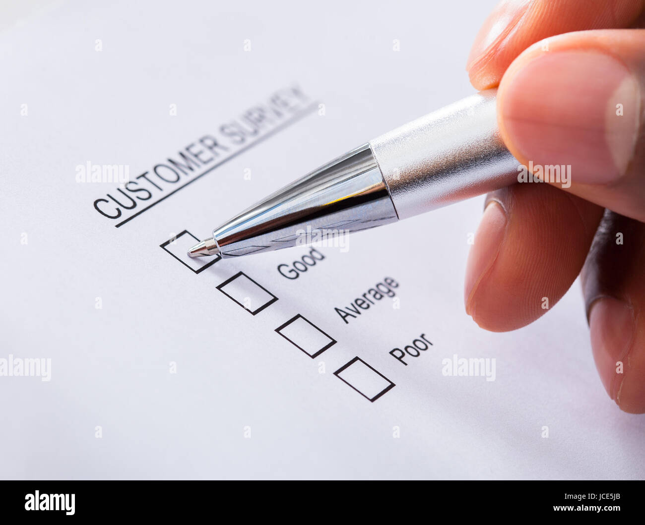 Close-up Of Human Hand Filling Customer Survey Form Stock Photo