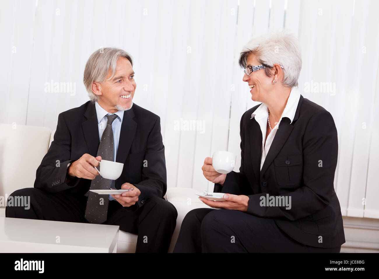 Smiling relaxed senior business colleagues taking a well earned coffee break - Stock Image
