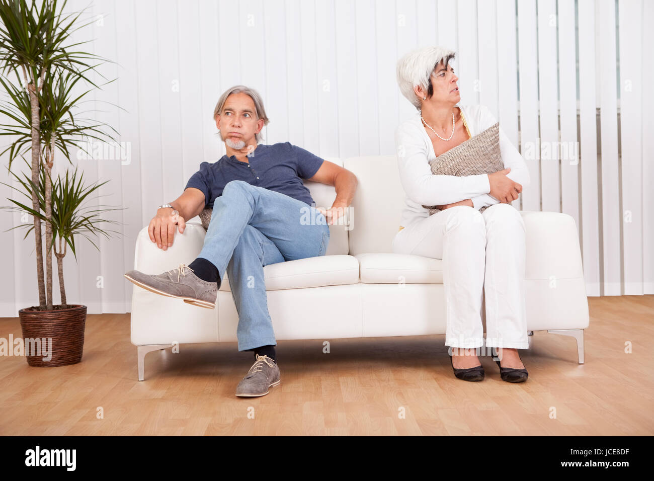 Senior couple after an argument sitting at opposite ends of the sofa sulking and looking away from each other into - Stock Image