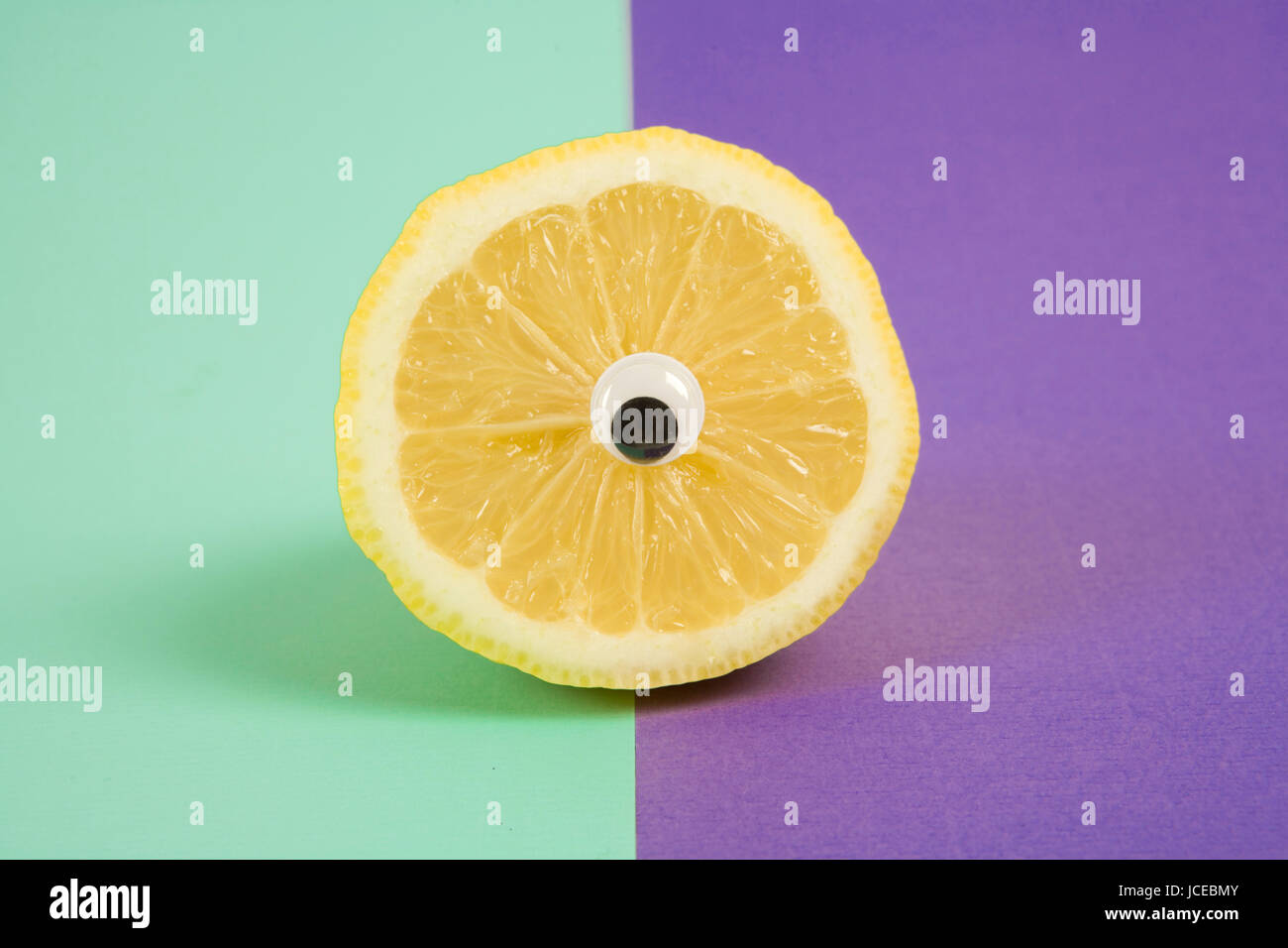 Minimal still life photography.An lemon cut in half and wearing doll's eyes like a cyclop. pop bi colored background - Stock Image