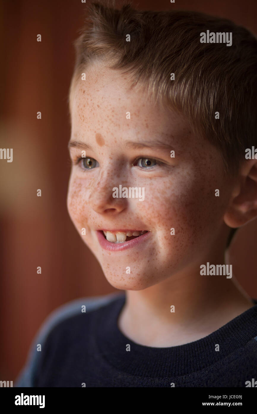A happy and bright 9 year old boy during a family outing. - Stock Image
