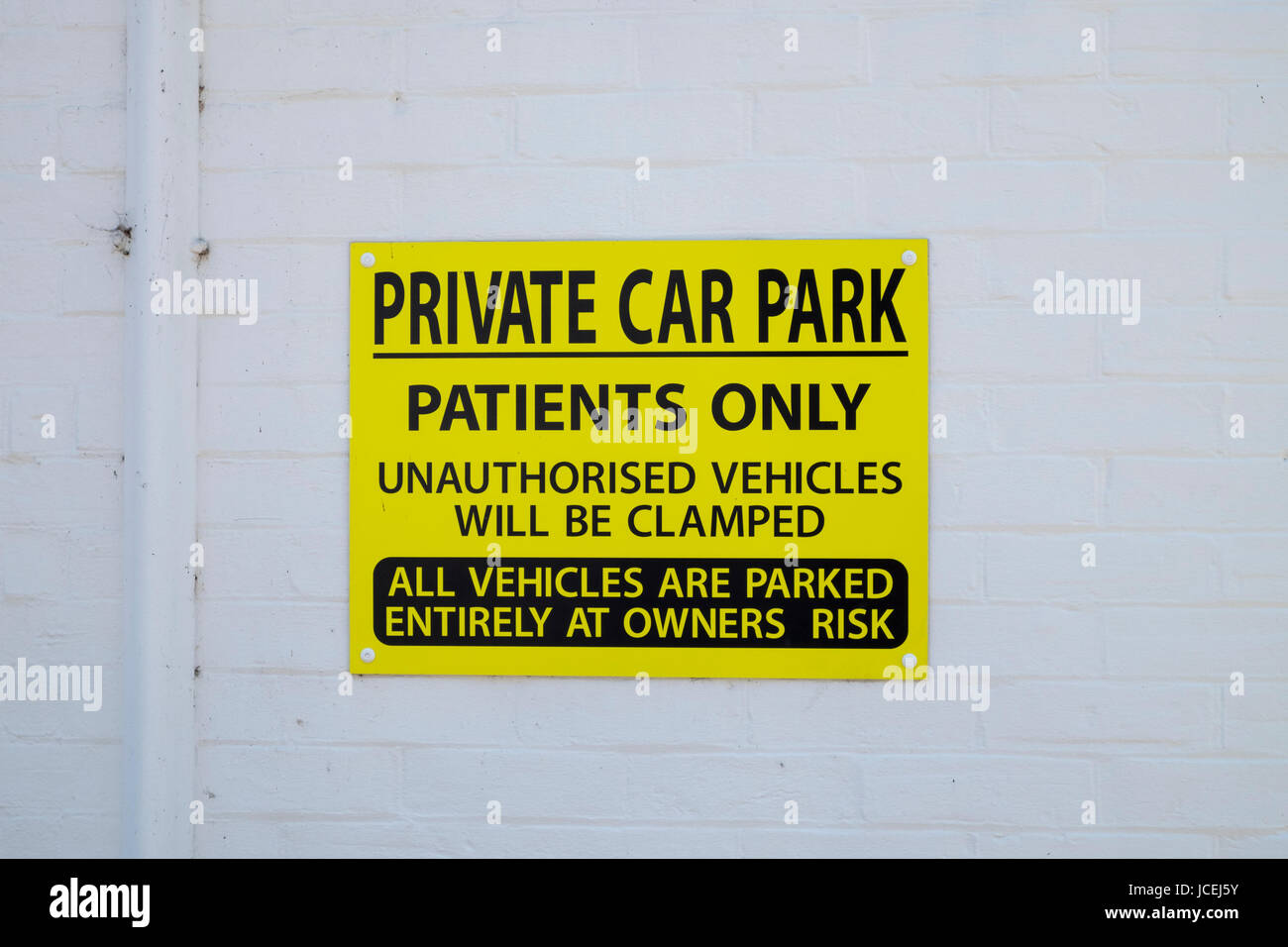 bright yellow private car park patients only sign signage. Ashford, Kent Stock Photo