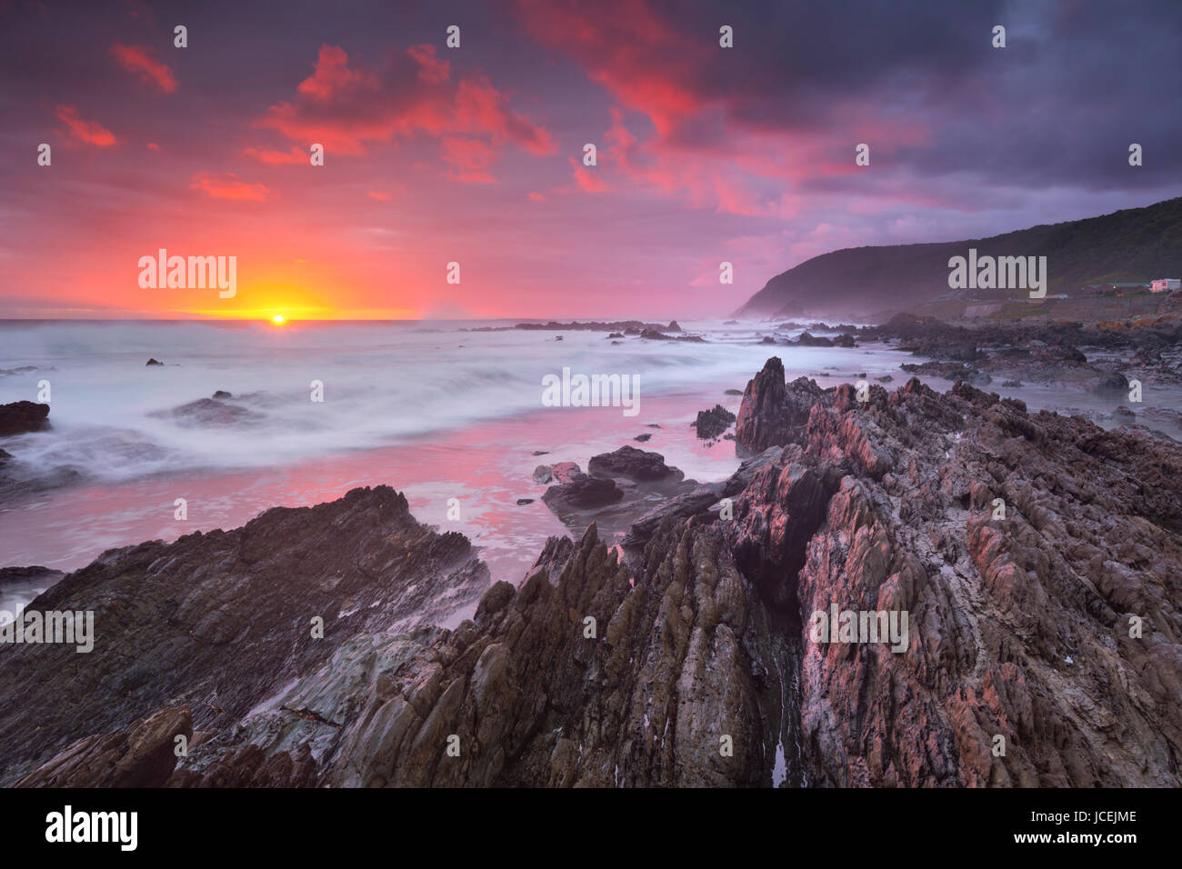 Spectacular sunset over the rocky coastline of the Tsitsikamma section of the Garden Route National Park, South - Stock Image