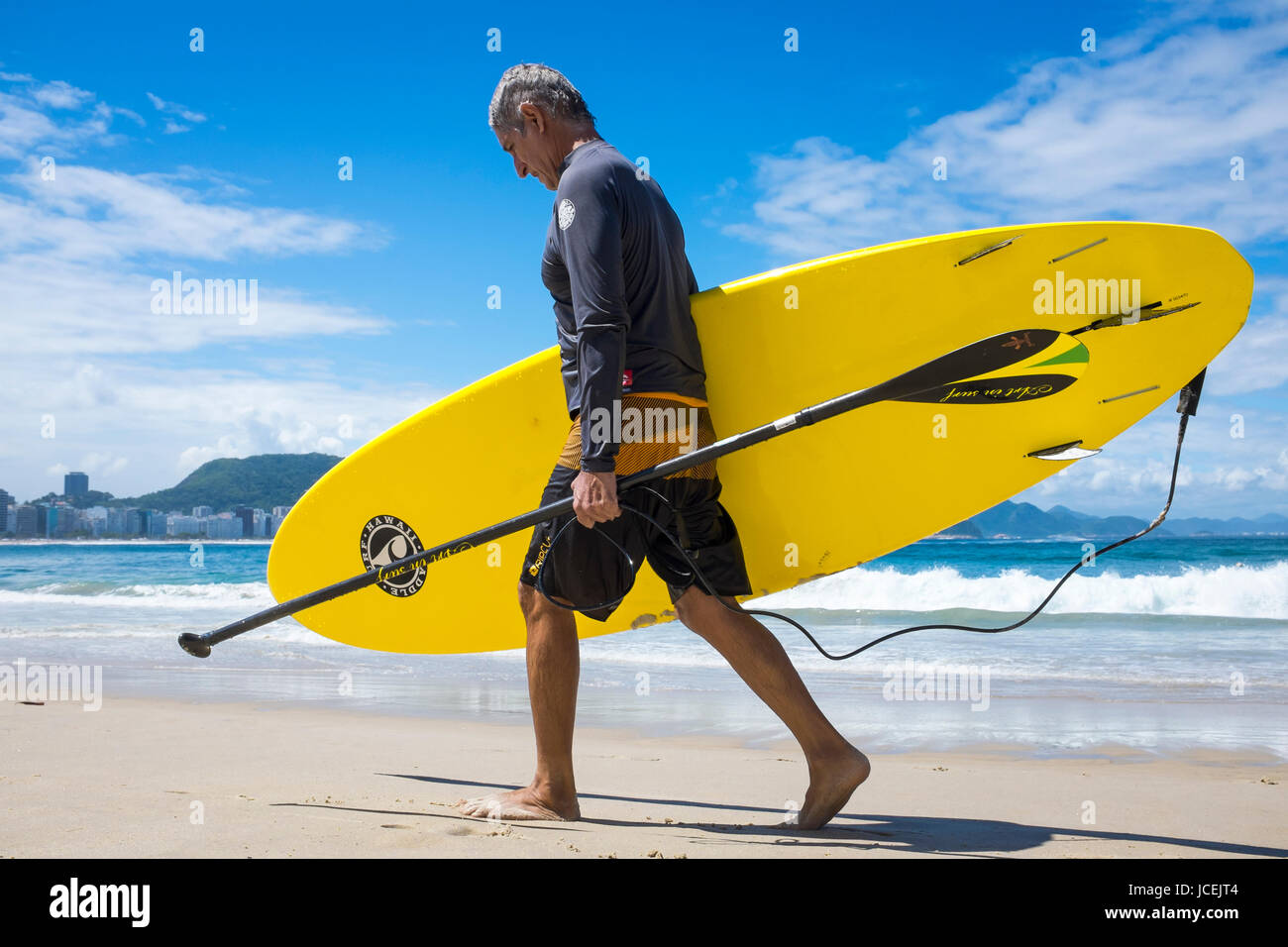 RIO DE JANEIRO - MARCH 21, 2017: Brazilian man walk along Copacabana Beach carry his stand-up paddle board and oar. - Stock Image