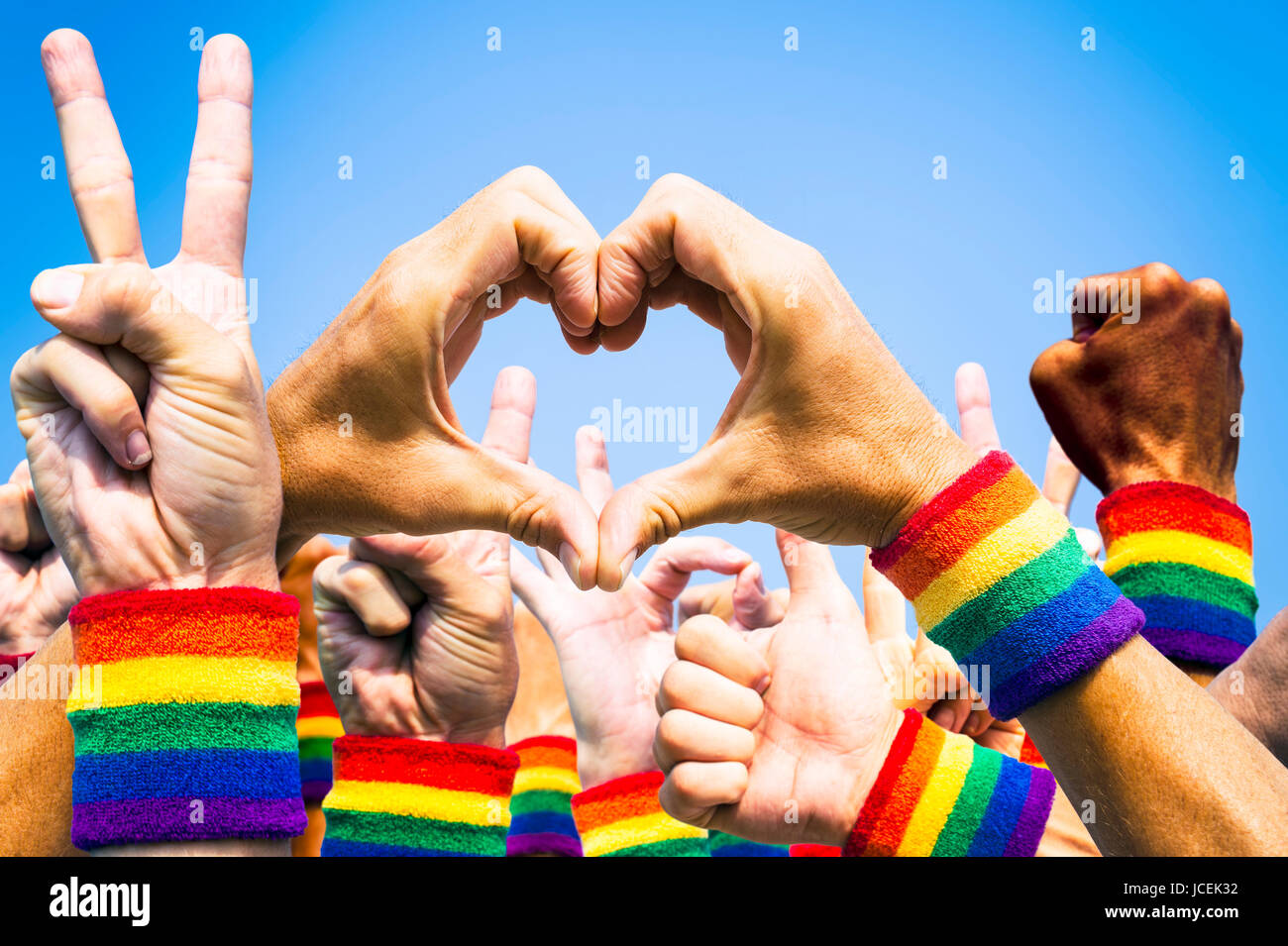 Crowd of hands making supportive signals at gay pride parade - Stock Image